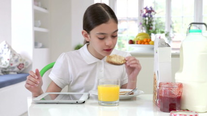 Hispanic Schoolgirl With Digital Tablet Eating Breakfast