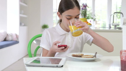 Schoolgirl With Digital Tablet And Mobile Eating Toast