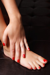 Close-up portrait of painted nails and toes with red nail polish