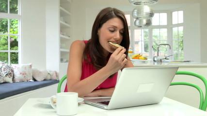Hispanic Woman Using Laptop In Kitchen At Home