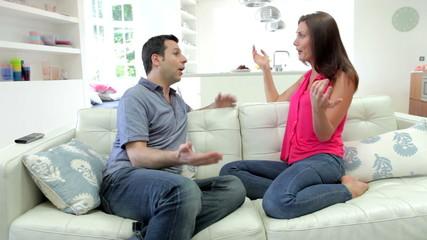 Hispanic Couple Sitting On Sofa Having Argument