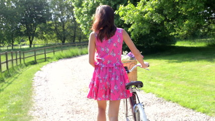 Attractive Woman Pushing Cycle Along Country Lane
