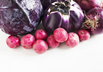 Сollection of fresh purple toned vegetables on white wooden bac