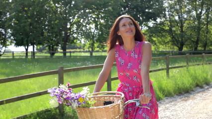 Attractive Woman Riding Bike Along Country Lane