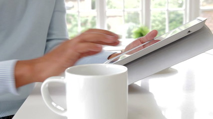 Close Up Of Man Using Digital Tablet Whilst Eating Breakfast