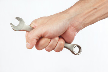 Hand of repairman with a wrench on a white background