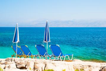 Sunbeds and umbrellas on a rocky beach in Corfu Island, Greece