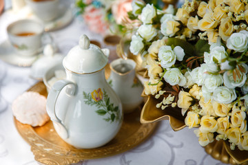 Flowers, tea, marshmallows on a tray on the table