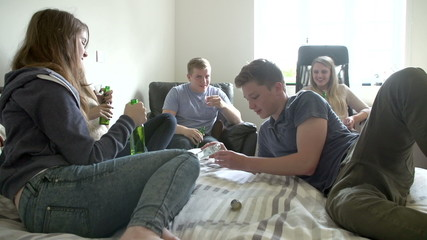 Group Of Teenager Drinking Alcohol In Bedroom