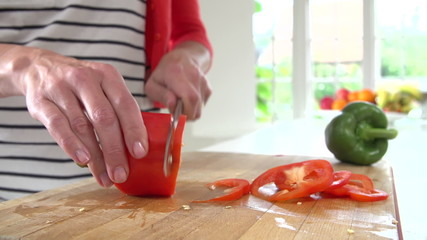 Close Up Of Woman Chopping Peppers On Wooden Board