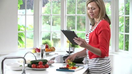Woman Following Recipe On Digital Tablet Whilst Cooking