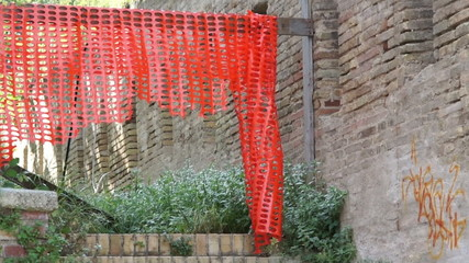 Red plastic fence on the reconstruction of the ancient walls
