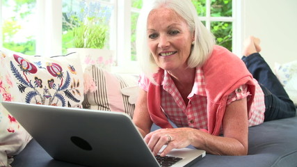 Middle Aged Woman Using Laptop Lying On Sofa