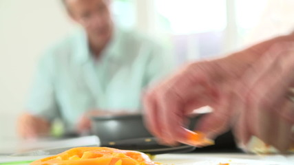 Close Up Of Woman Chopping Peppers And Adding To Frying Pan