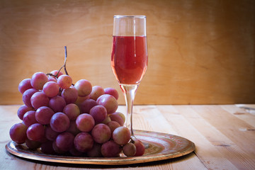 pink grapes and a glass of wine on a metal tray