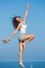 Barefoot girl dancing on seashore