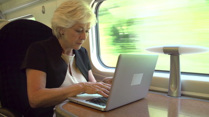 Businesswoman Commuting To Work On Train And Using Laptop