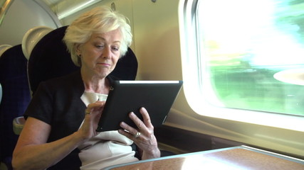 Businesswoman Commuting On Train Using Digital Tablet
