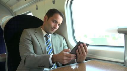 Businessman Commuting On Train Reading E Book
