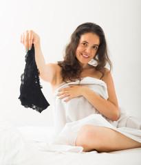 Brunette undressing in bedroom