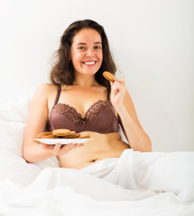 Woman eating cookies in bed