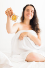 Happy woman holding  condom in bed