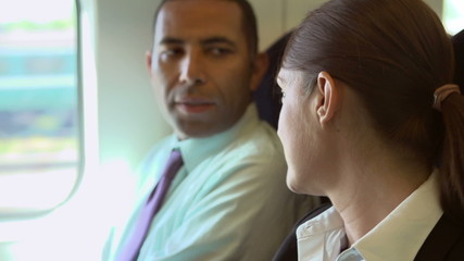 Close Up Of Two Businesspeople In Conversation On Train
