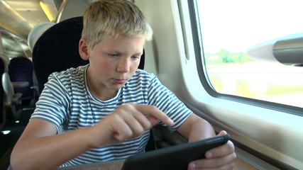 Boy Reading E Book On Train Journey