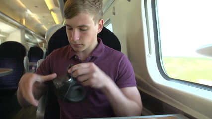 Young Man Listening To Music On Train Journey