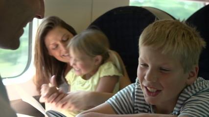Family Relaxing On Train Journey