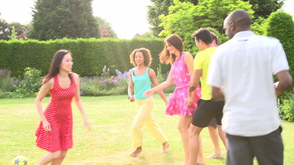 Slow Motion Sequence Of Friends Playing Football In Garden