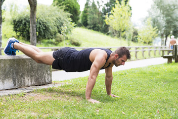 Athletic strong man doing pushups, outdoor.