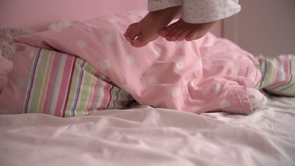 Slow Motion Sequence Of Young Girl's Feet  Jumping On Her Bed