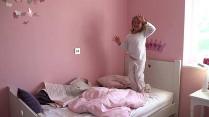 Slow Motion Sequence Of Young Girl Jumping On Her Bed