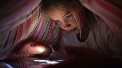 Girl Looking At Digital Tablet In Under Bed Cover At Night