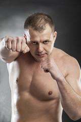man boxing half naked on grey background