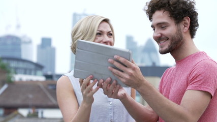 Couple In Urban Setting With Digital Tablet Taking Photo