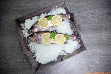 Frische Forelle mit Limone auf einem Holztablett