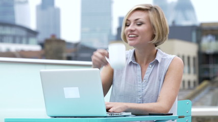 Young Woman Sitting On Roof Terrace Using Laptop
