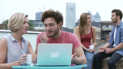 Group Of Friends Relaxing Together On Rooftop Terrace