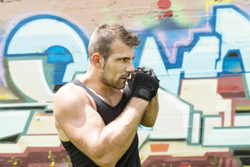 Athletic man fighter in boxing pose, urban style.