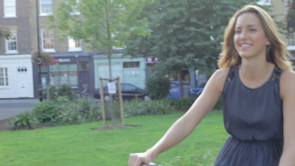 Businesswoman Riding Bike Through City Park