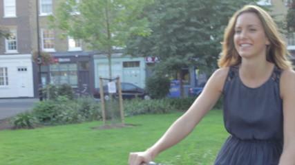 Businesswoman Riding Bike Through City Park