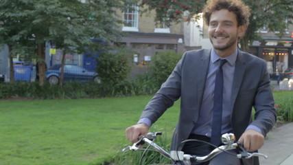 Businessman Riding Bike Through City Park