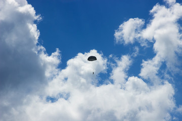 Silhouette of skydiver at blue sky