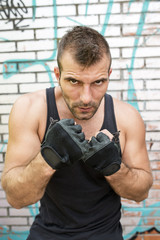 Portrait of serious man fighter in boxing pose, urban style.