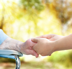 Senior lady in wheel chair holding hands with young caretaker