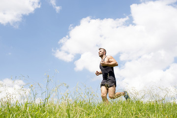 Strong athletic man running on the field.