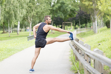 Athletic man doing stretches before exercising, outdoor.