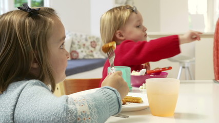 Two Young Children Eating Meal At Home